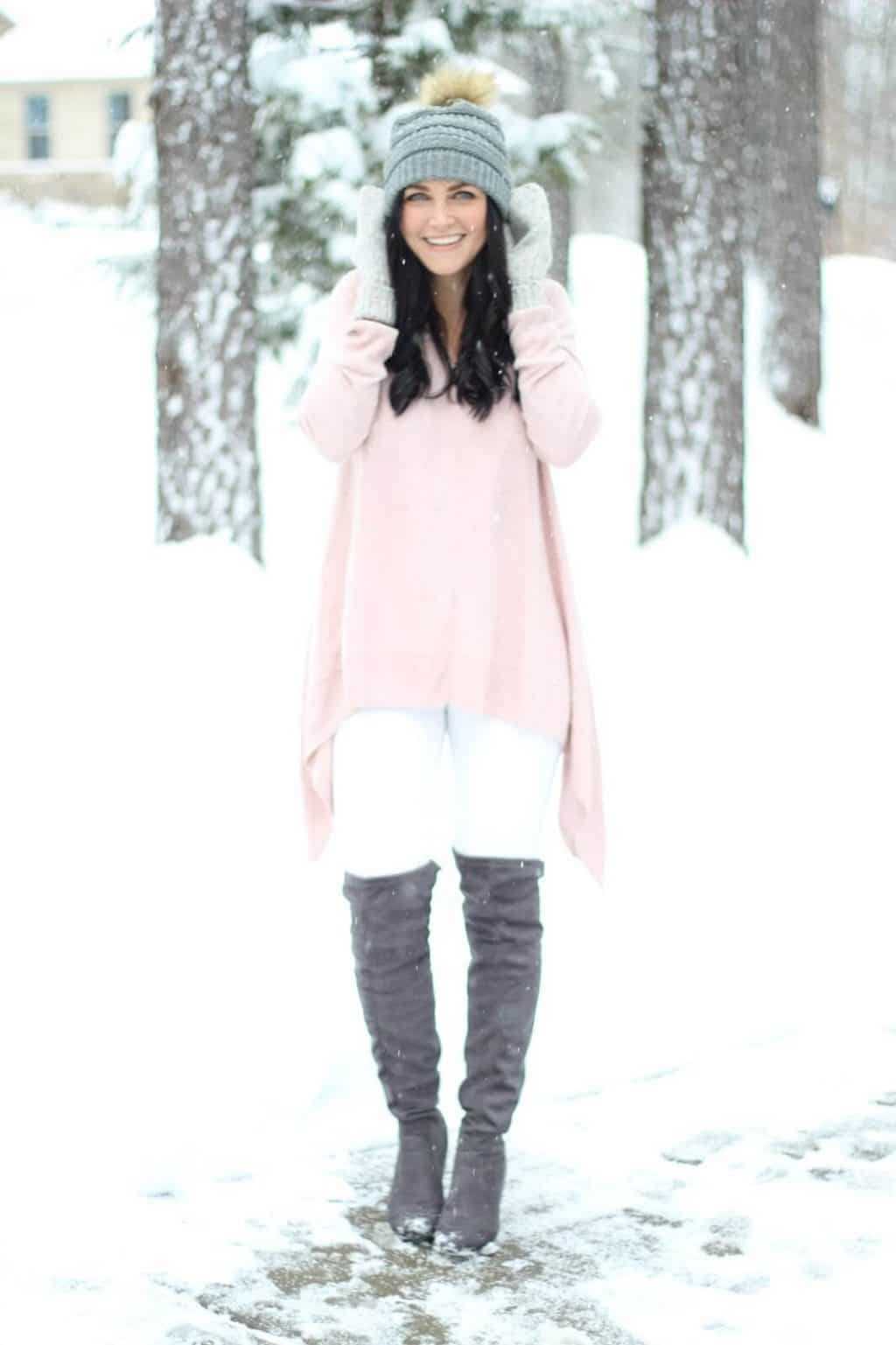 Pom beanie, white jeans, over the knee boots in the snow